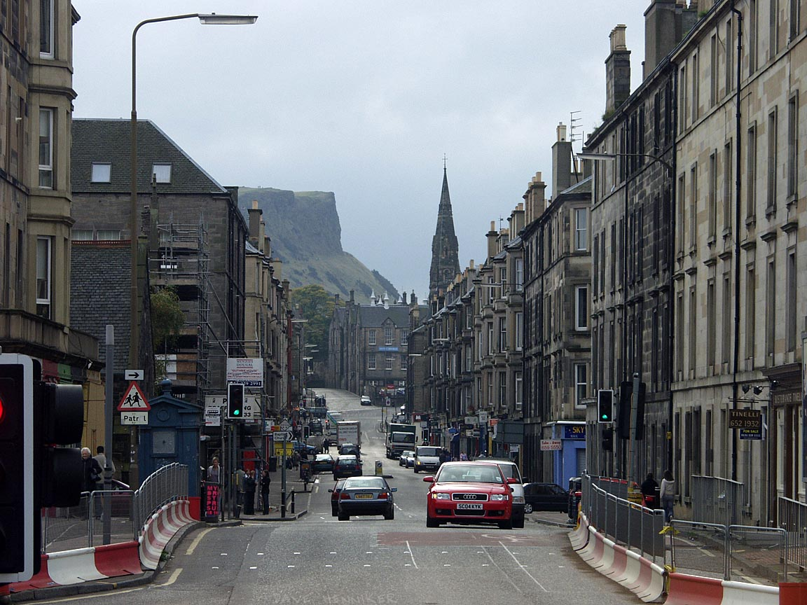 The railway line which passes under here has remained in use solely for transporting rubbish to Powderhall. The bridge has been weakened and road traffic restricted to one way to reduce the load. Salisbury Crags tower above in the distance behind Abbeyhill Tech Base. Those tiny dots, 4 pixels high, are people walking on the crags.