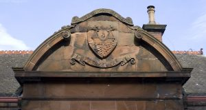 A close up shot of the shield and motto carved in the red sandstone over the entrance to the Swim Centre (or Victorian Public Baths).