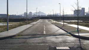 A shiny new road leads across a flooded wasteland to an embankment of mud. Beyond is the familiar outline of Arthur's Seat and the city of Edinburgh.