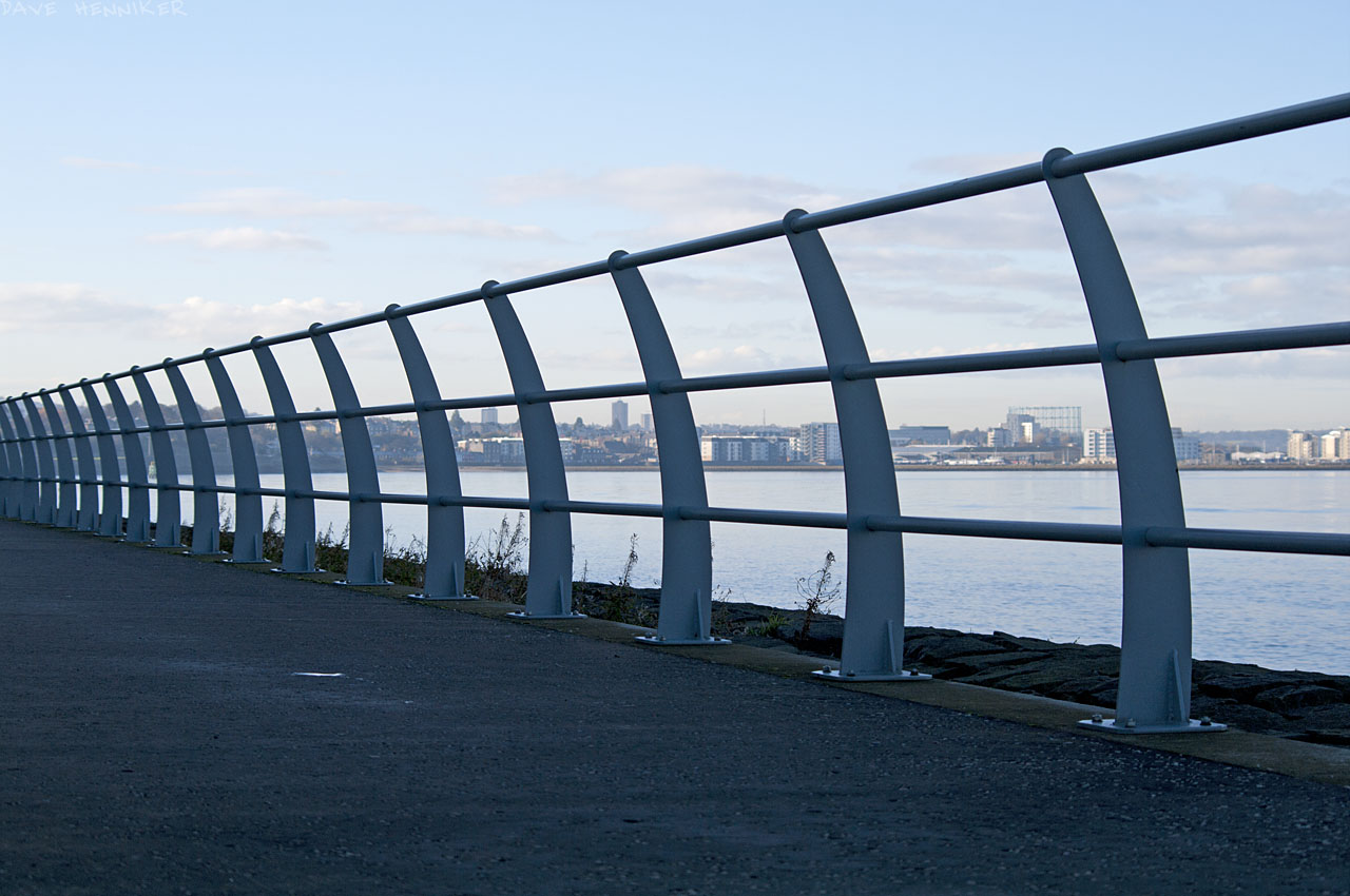 A sturdy fence runs the length of the heavily fortified sea wall. Granton Gasworks' remaining gasometer is in the distance to the west.