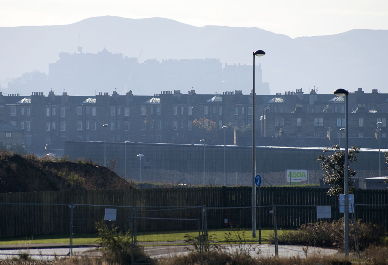Zoomed in on the the grey silhouettes of the castle and Caerketton Hill in the Pentlands. The Asda superstore at Newhaven stands in front.