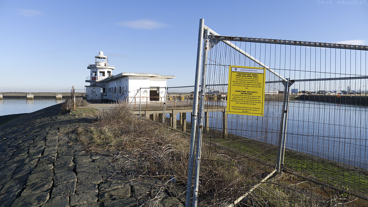 A futile attempt at keeping people out with a fence is augmented by a yellow warning notice.