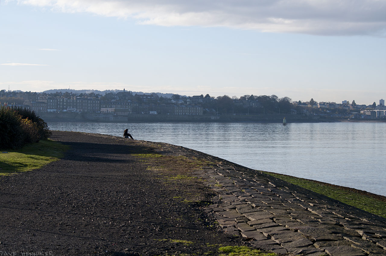Where the sea wall curves sits a woman, maybe drawing or painting.