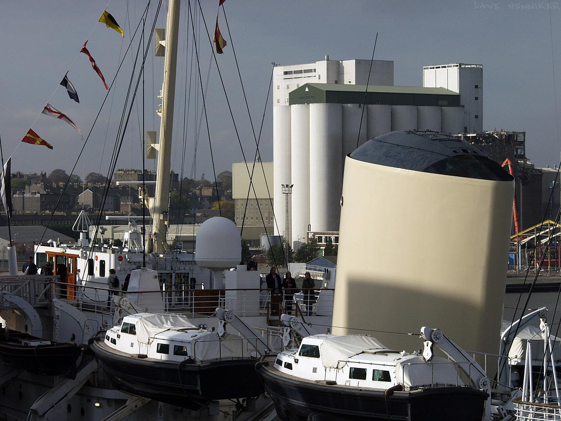 The Royal Yacht Britannia has its entrance and visitor centre within the Ocean Terminal building. The yacht's funnel, though big compared to the lifeboats, is dwarfed by Chancelot Flour Mill half a kilometre to the west.