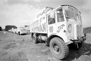 A line of circus vehicles on waste ground.