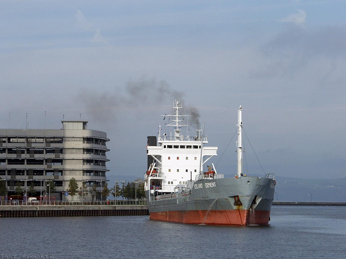 Debenham's grey waterside building is colour-matched with a passing ship emblazoned with the legend 'Iceland Cement'.