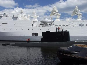 Three vessels in the docks. A submarine is travelling backwards towards Western Harbour with the assistance of a tug. An enormous ship resplendent with countless satellite dishes and radio antennae forms the background.