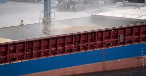 The cargo is sprayed into the ship's hold supervised by a man in a yellow jacket.