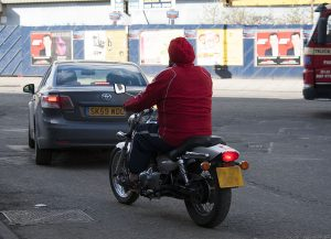 Emerging from Albert Street into Leith Walk is a motorcyclist who doesn't have to wear a helmet.