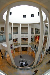 A vertical fisheye view of the atrium. The man at the bottom of the picture is directly below but we can still see the top of the building where the sunlight is filtering in.