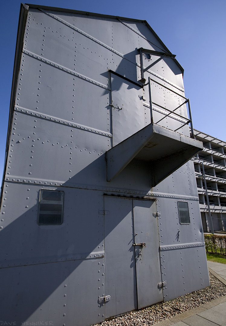 The front of the building is quite imposing, with the metal plates and rivets catching the sunlight. The purpose of the upper door on its little balcony eludes me, as does everthing else about this strongbox construction. The upper door has some large dents in it made from the inside...