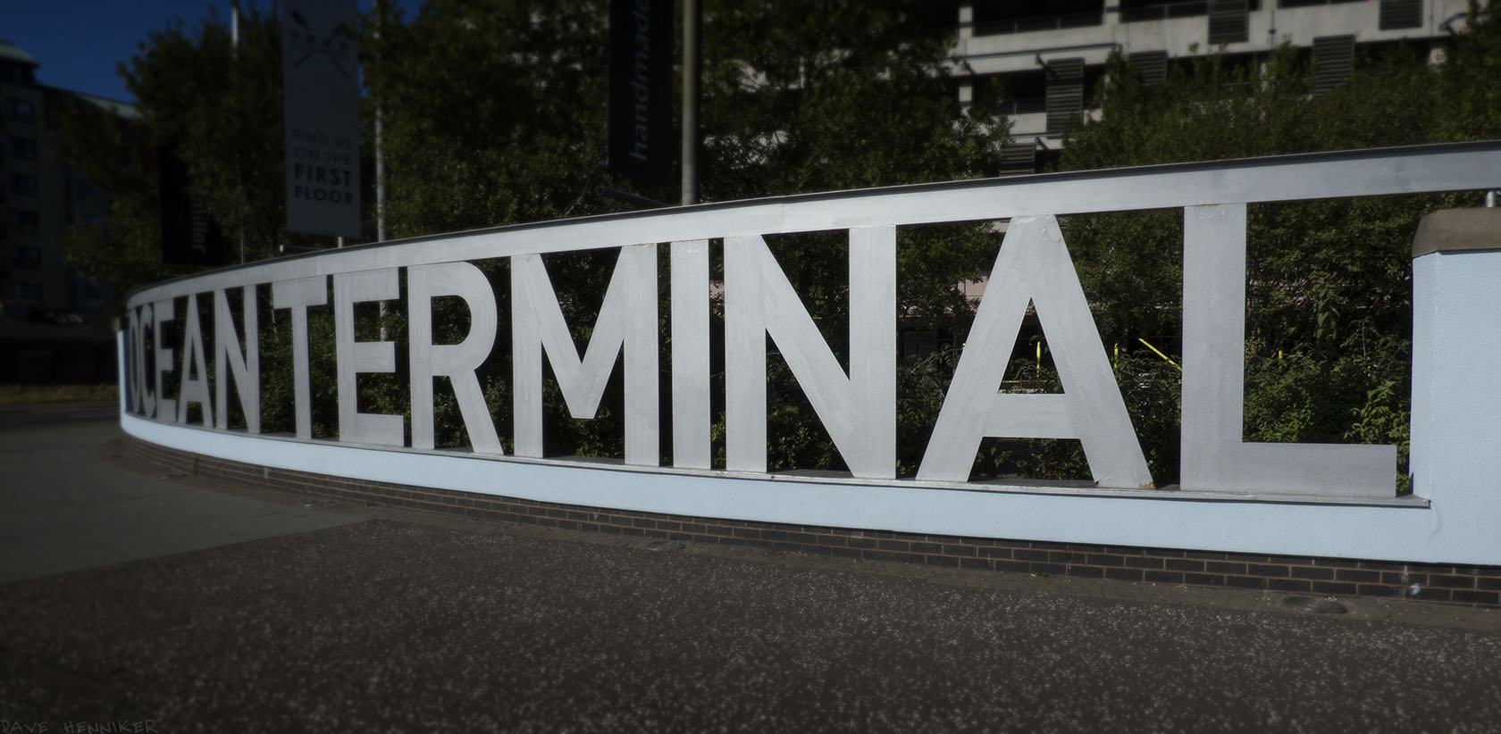 A metal fence made from the letters of Ocean Terminal.
