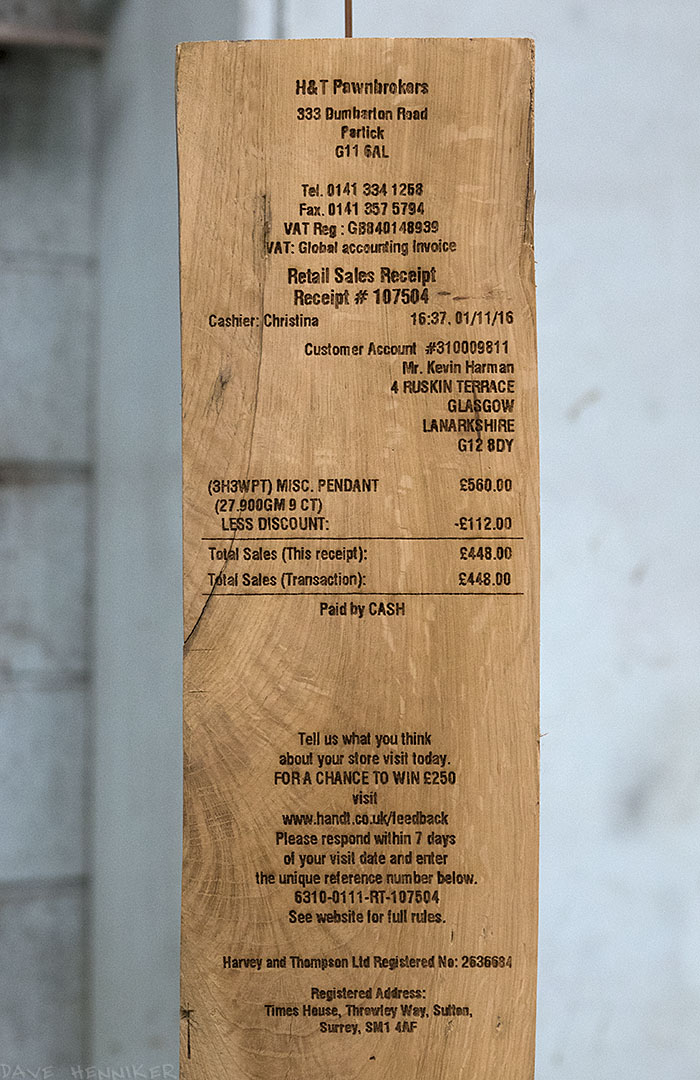 The first of 3 photos of wooden posts imprinted with pawnbrokers' receipts.